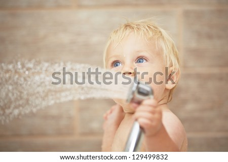 Blond baby in the bathroom - stock photo