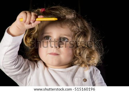 Blond baby playing on black background