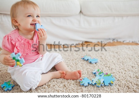 Blond baby playing with puzzle pieces while sitting on a carpet in the living room - stock photo