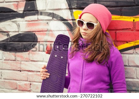 Blond beautiful teenage girl holds skateboard near by urban wall with colorful graffiti