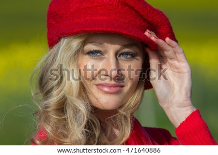 blond beautiful white woman wearing a bright red hat outdoors