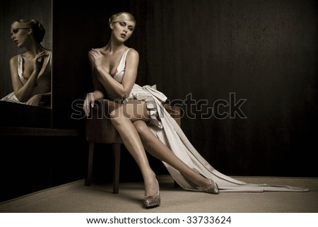 Blond beautiful woman beside mirror - stock photo