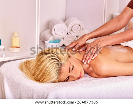 Blond beautiful woman getting  back massage. Visible hand masseuse - stock photo