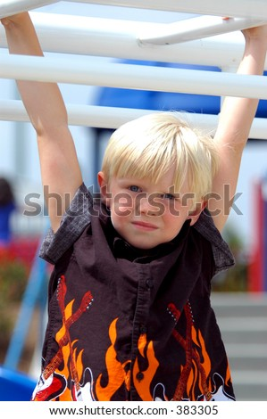 Blond boy child in a rock and roll flame shirt playing on the monkey bars at a local playground - stock photo