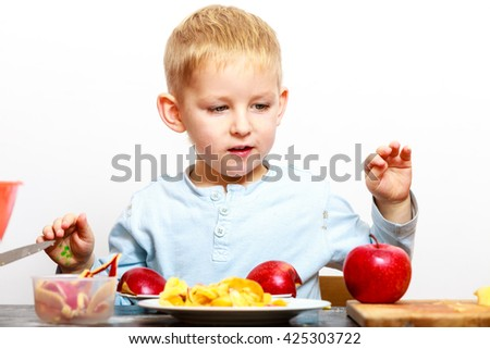 Blond boy child kid preschooler peeling fruit apple eating cooking at home. Happy childhood.