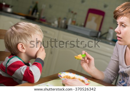 Blond Boy Holds Hand on his Mouth to Stop Eating - stock photo