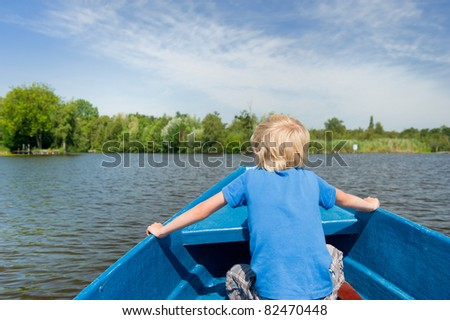 Blond boy in blue boat on the water - stock photo