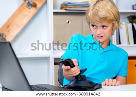 blond boy is playing computer game in his room - stock photo