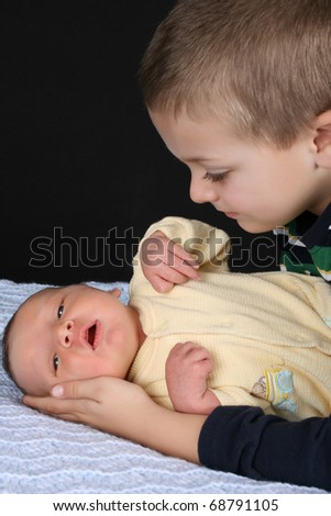 Blond boy looking at his newborn baby brother