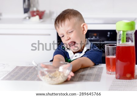 Blond Boy Making Disgusted Face and Pushing Away Bowl of Oatmeal Cereal at Breakfast Time While Sitting at Kitchen Table with Glass of Red Juice - stock photo