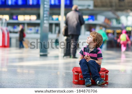 Blond boy of 4 years sitting on suitcase at the airport, indoors and waiting for going on vacations. - stock photo