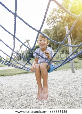 Blond boy playing on a children's playground and has fun