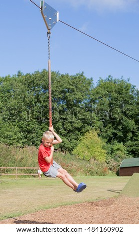 Blond boy riding on a zip wire
