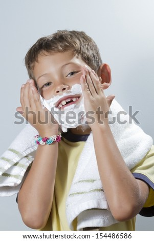 Blond boy with missing tooth smile while placing shaving cream with both hands - stock photo
