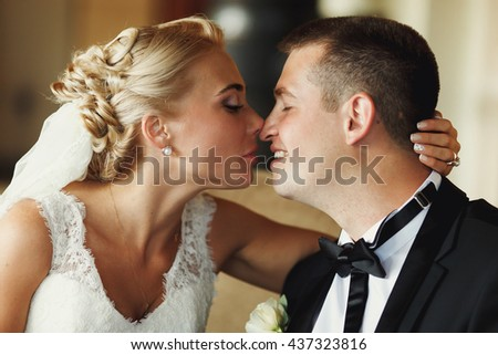 Blond bride touches groom's nose tenderly holding his head