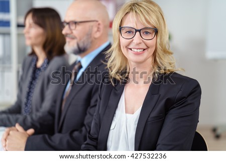 Blond business woman in suit jacket smiles at camera while seated next to others in a conference - stock photo