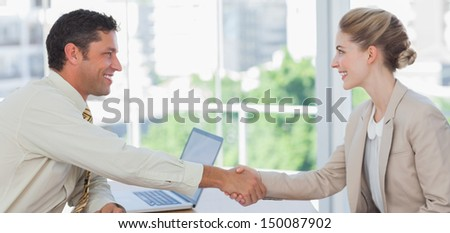 Blond businesswoman having an interview in office and shaking hands with interviewer - stock photo
