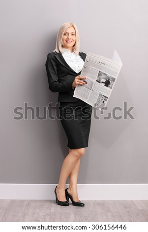 Blond businesswoman holding a newspaper and looking at the camera.The newspaper is custom made, text is Latin and the pictures are my copyright. Additionally property release uploaded. - stock photo