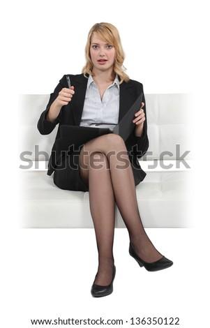 Blond businesswoman sat in chair - stock photo