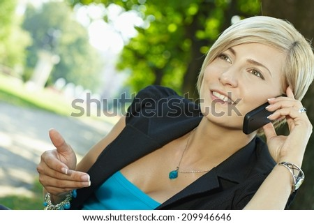 Blond caucasian businesswoman gesturing and talking on mobile phone at outdoor park. Smiling, happy, wearing woman suit. - stock photo