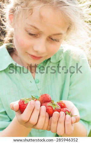 Blond caucasian seven years old child girl holding strawberries in hands. Spring - fresh harvest from the garden. Happy childhood concept. - stock photo