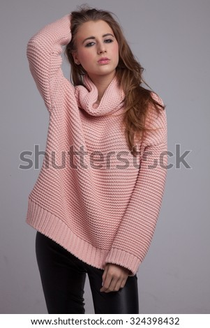 Blond cheerful young pretty woman. Beauty portrait, perfect makeup. Long chic elegant hair. Model tests. Cute girl in pink sweater. Isolated. Gray background. - stock photo