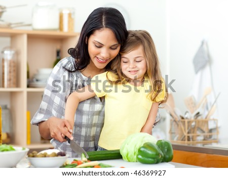 Blond child cutting vegetables with her mother in the kitchen - stock photo