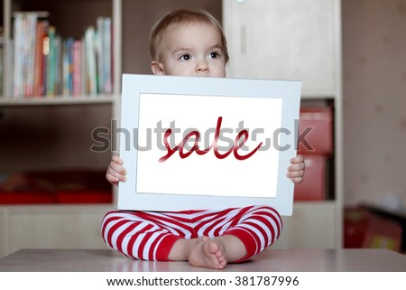 Blond child holding empty blank white frame to put words on a home background, presentation and ad concepts, indoor - stock photo