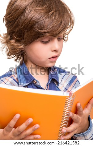 Blond cute boy reading a book over white