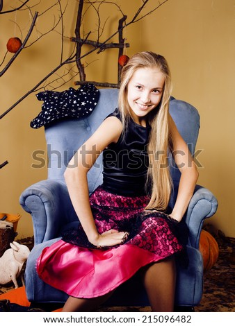 blond cute girl in halloween interior with pumpkin, cute teen smiling - stock photo