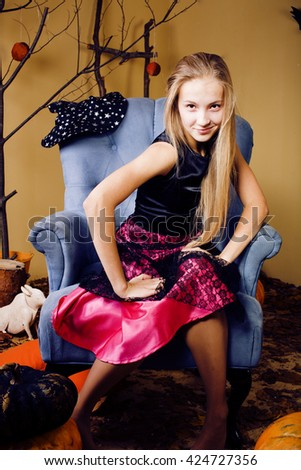 blond cute girl in halloween interior with pumpkin smiling close up - stock photo