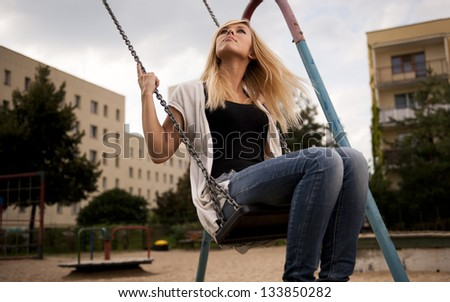 Blond cute girl on a swing - stock photo