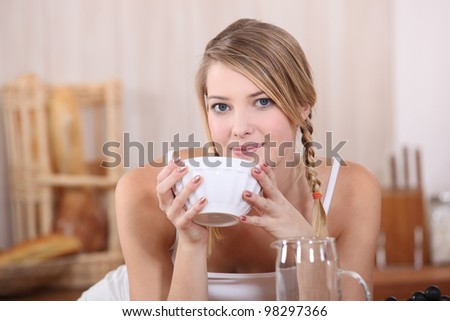 Blond drinking from bowl at breakfast