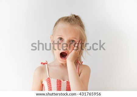 Blond European girl staring at the camera in white background. Amazed kid opening her mouth in surprise and putting her hand on her cheek. Shocked and puzzled facial expression.