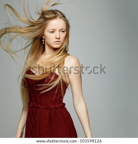 Blond fashion model posing with hair fluttering in the wind - stock photo