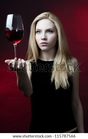 blond female fashion model holding wine glass posing at red background - stock photo