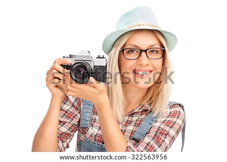 Blond female photographer with a blue cap holding a camera and posing isolated on white background - stock photo