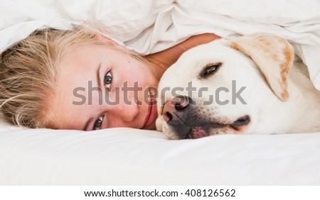 Blond girl and Labrador dog snuggling under a white duvet on a bed.