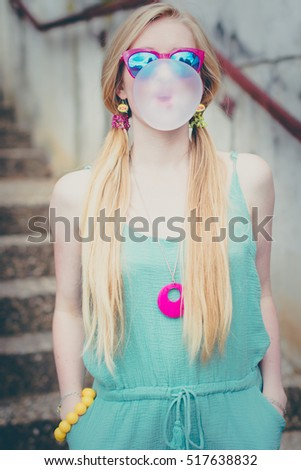 Blond girl chewing gum and making bubbles