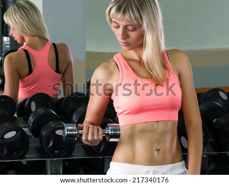 blond girl doing athletic exercise with dumbbells in sport hall on mirror background - stock photo