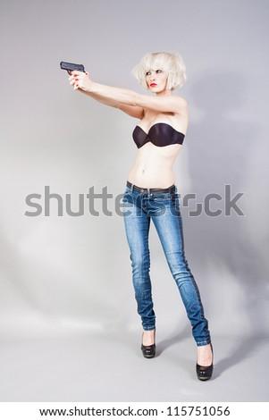 Blond girl holding a gun - stock photo