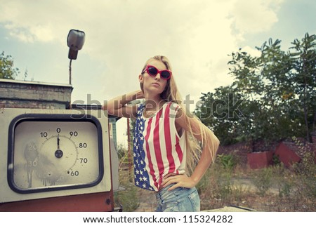 Blond girl holds hands on her head standing on damaged gas station - stock photo