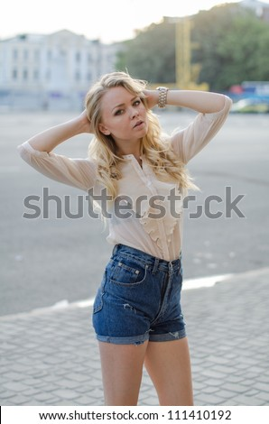 Blond girl in a  blue jeans shorts and white blouse  posing on the street - stock photo