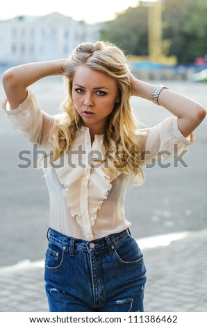 Blond girl in a blue jeans shorts  posing on the street - stock photo