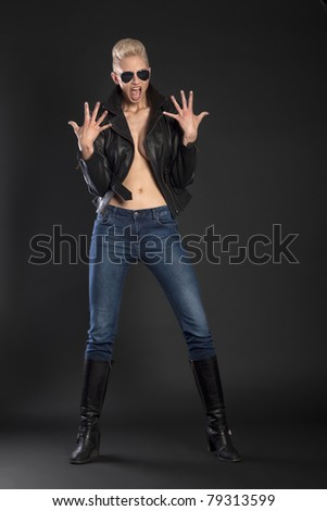Blond girl in leather jacket and jeans with sunglasses yelling - stock photo