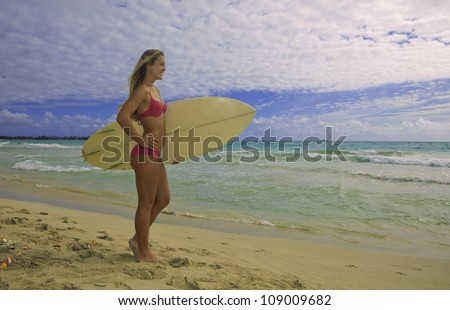blond girl in pink bikini with surf board watching the waves - stock photo