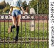 Blond girl in short shorts and denim coat with roses wreath on head turns back having climbed fence with skateboard hung on it - stock photo