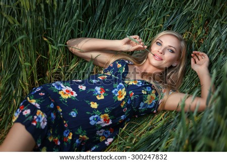 Blond Girl lying in the grass and smiling. Girl has blue eyes. - stock photo