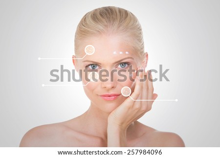 blond girl on grey background with cream on her face
