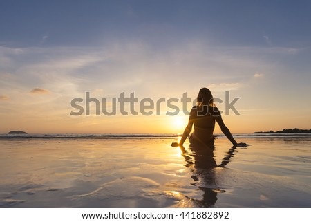 Blond girl on vacation relaxing on the beach and looking at sunset